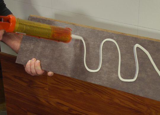 Нанесение клея на ламинат при монтаже на стену
