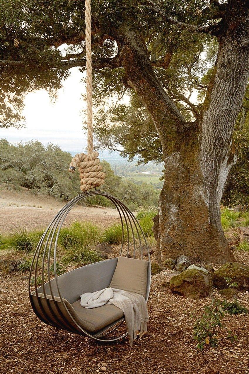 Металлические качели-лежак на дереве